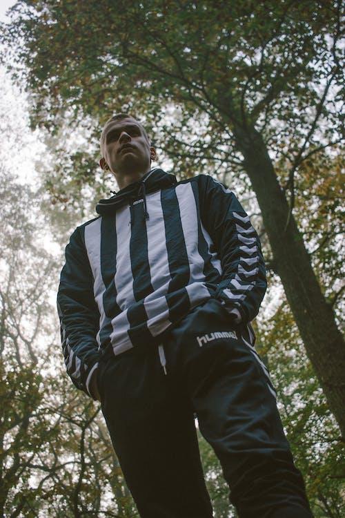 Man in striped wear near overgrown trees