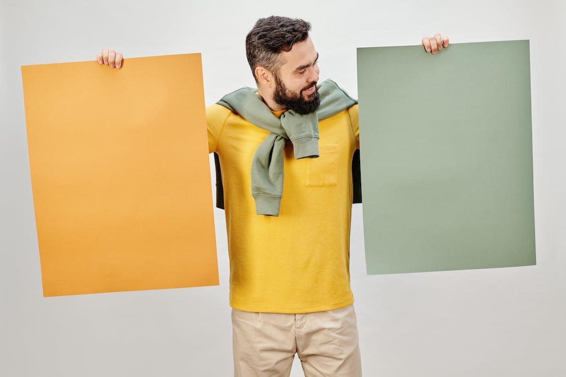 Man in Yellow Long Sleeve Shirt Holding Brown Folder