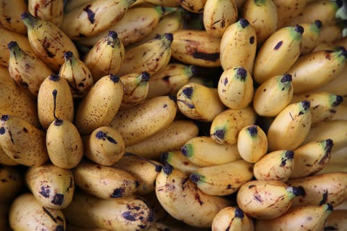 Background of delicious sweet ripe yellow unpeeled bananas fruits with dark spots in light place