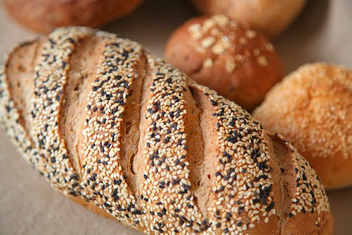 High angle of fresh baked bread with soft buns with sesame seeds served on surface in light place