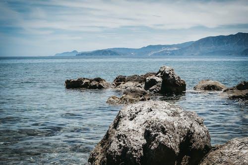 Rocky formations near blue rippling sea
