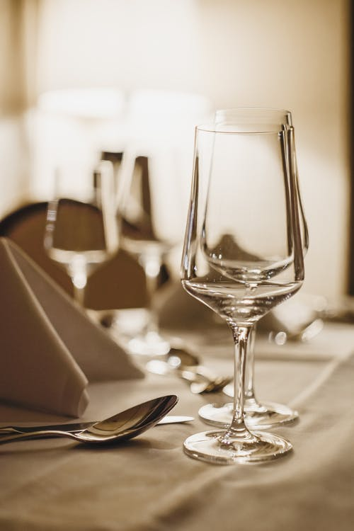 Crystal wineglasses and cutlery served on table