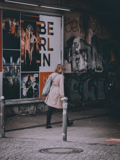 Woman in White Coat Standing in Front of Graffiti Wall