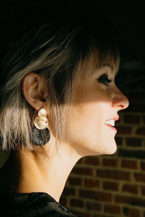 Smiling woman in modern earring near brick wall in house
