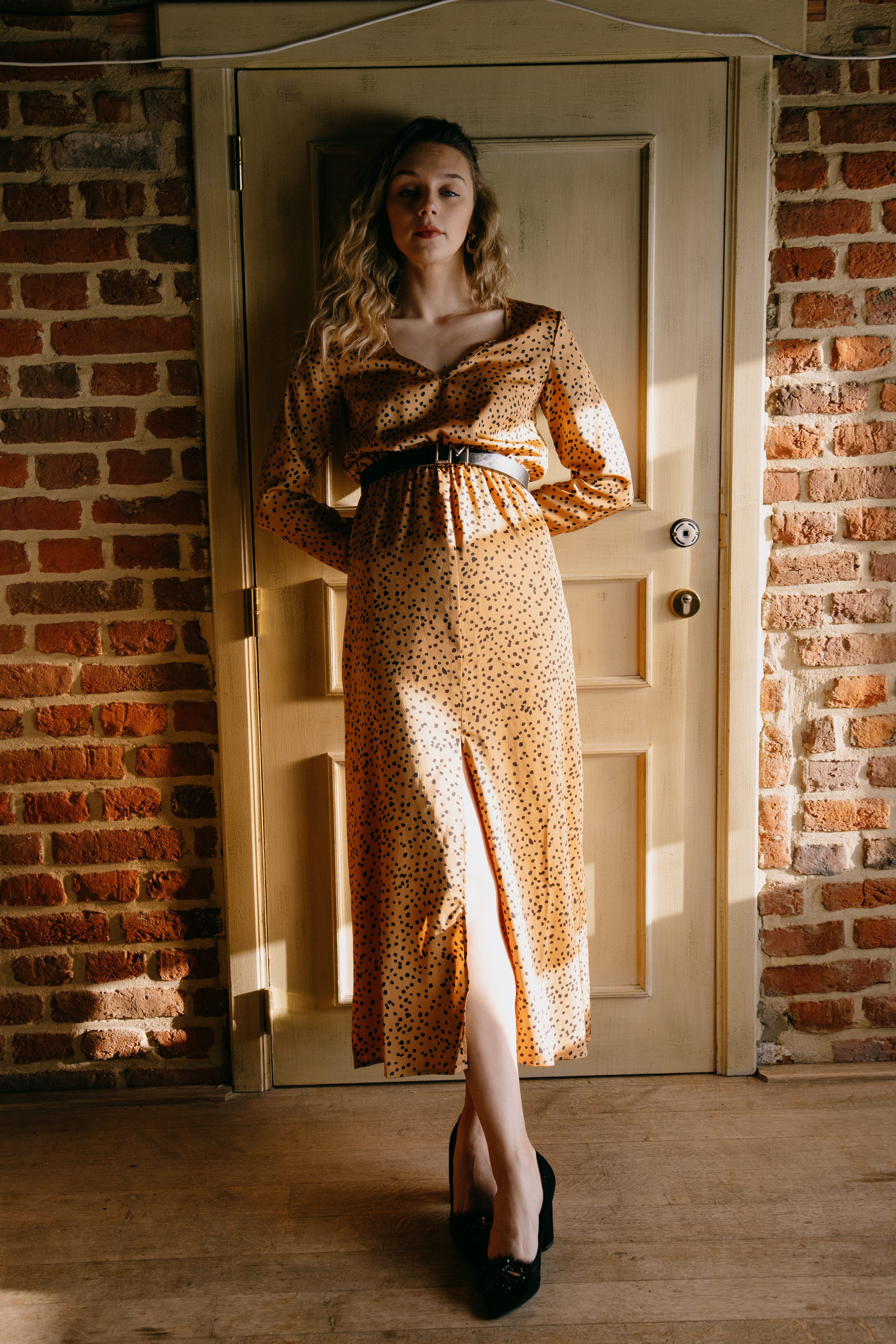 elegant dreamy woman in dress leaned on door at home