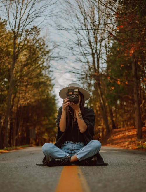 Woman Holding A Camera Sitting In The Middle Of The Road
