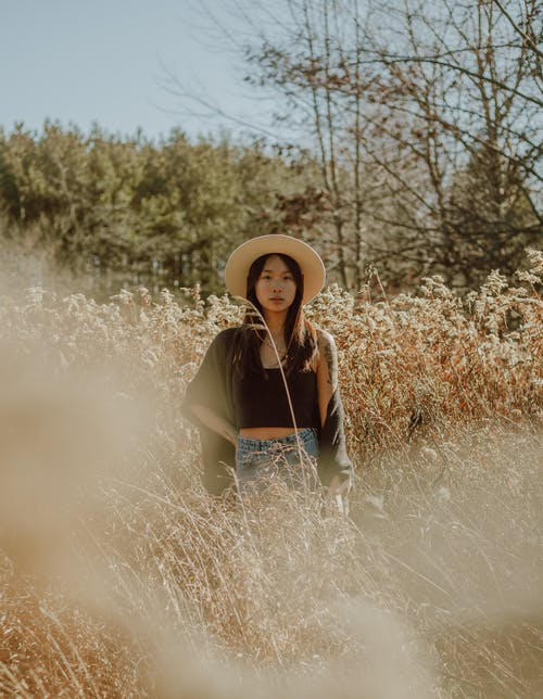 Serene Asian woman standing in lush meadow