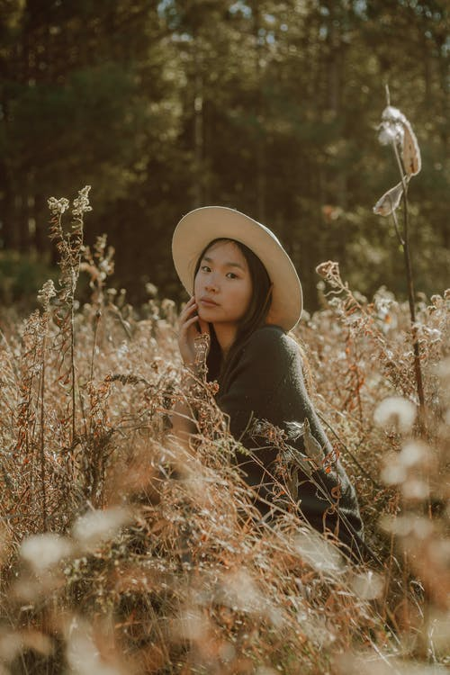 Charming Asian woman in hat resting on grassy meadow