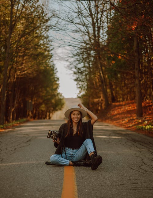 Full length delighted young Asian female wearing casual clothes and hat sitting on asphalt roadway with retro photo camera between yellow autumn trees