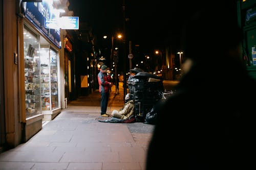 Anonymous man giving money to poor beggar on tiled sidewalk near shop showcases in town at dusk