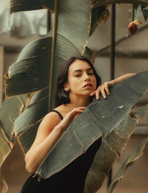 Mulher Atraente Perto De Uma Planta Tropical Exuberante