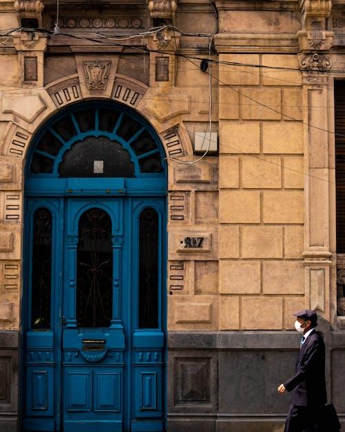 Человек в черном пальто стоит перед синей деревянной дверью