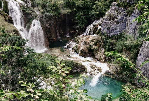 From above of amazing scenery of waterfall streaming among rough rocky cliffs covered with lush tropical vegetation and flowing into pond in jungle