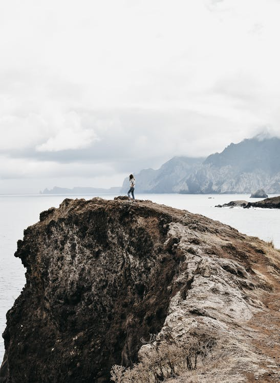 Distant unrecognizable female traveler relaxing on rough rocky cliff and admiring spectacular sea view against cloudy sky