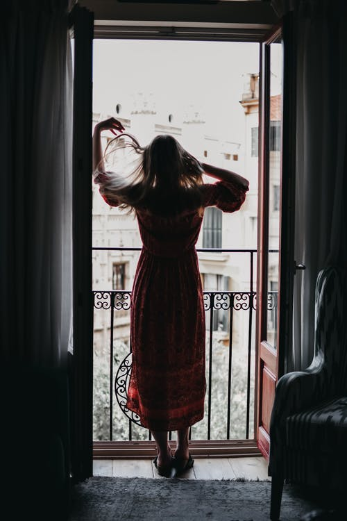 Unrecognizable woman touching hair and looking out balcony
