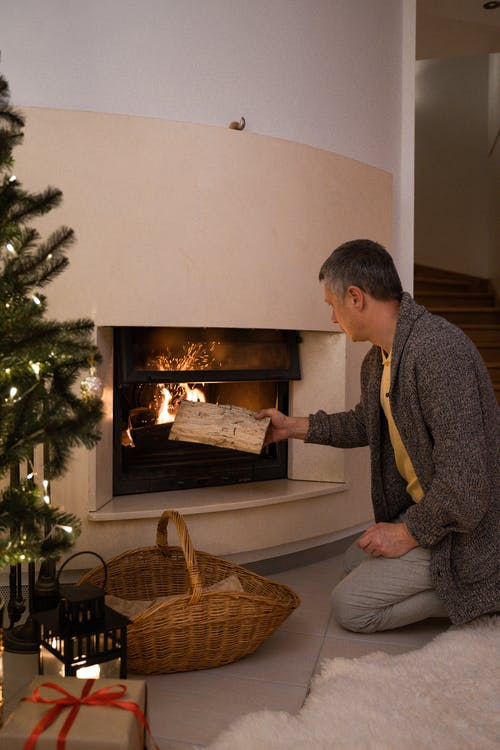 Man in Gray Sweater Standing Beside Fireplace