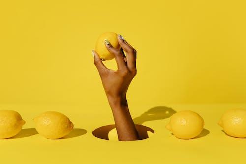 Osoba Trzymająca żółte Okrągłe Owoce