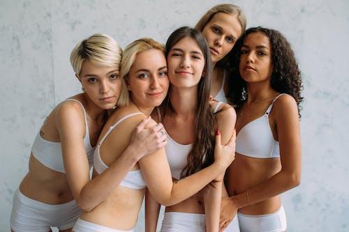3 Women in White and Brown Bikini Posing for Photo