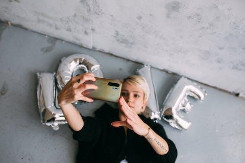 Donna In Camicia Nera A Maniche Lunghe Che Tiene Iphone 6 D'oro