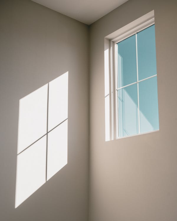 Low angle of window with glazing bars in light simple room with shadow on white wall