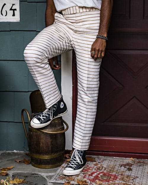 Person in White and Red Stripes Pants Wearing Black Sneakers