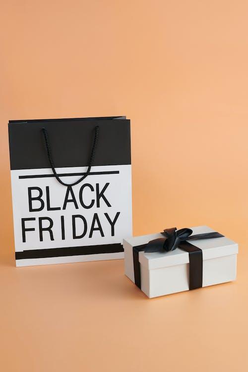 ブラックフライデーのテキストが入った黒と白の紙袋と黒のリボンが付いた箱