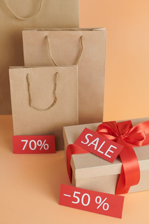 Brown Paper Bags and Cardboard Box with Sale Sign