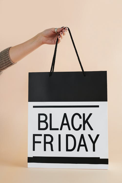Person Holding Black and White Black Friday Paper Bag
