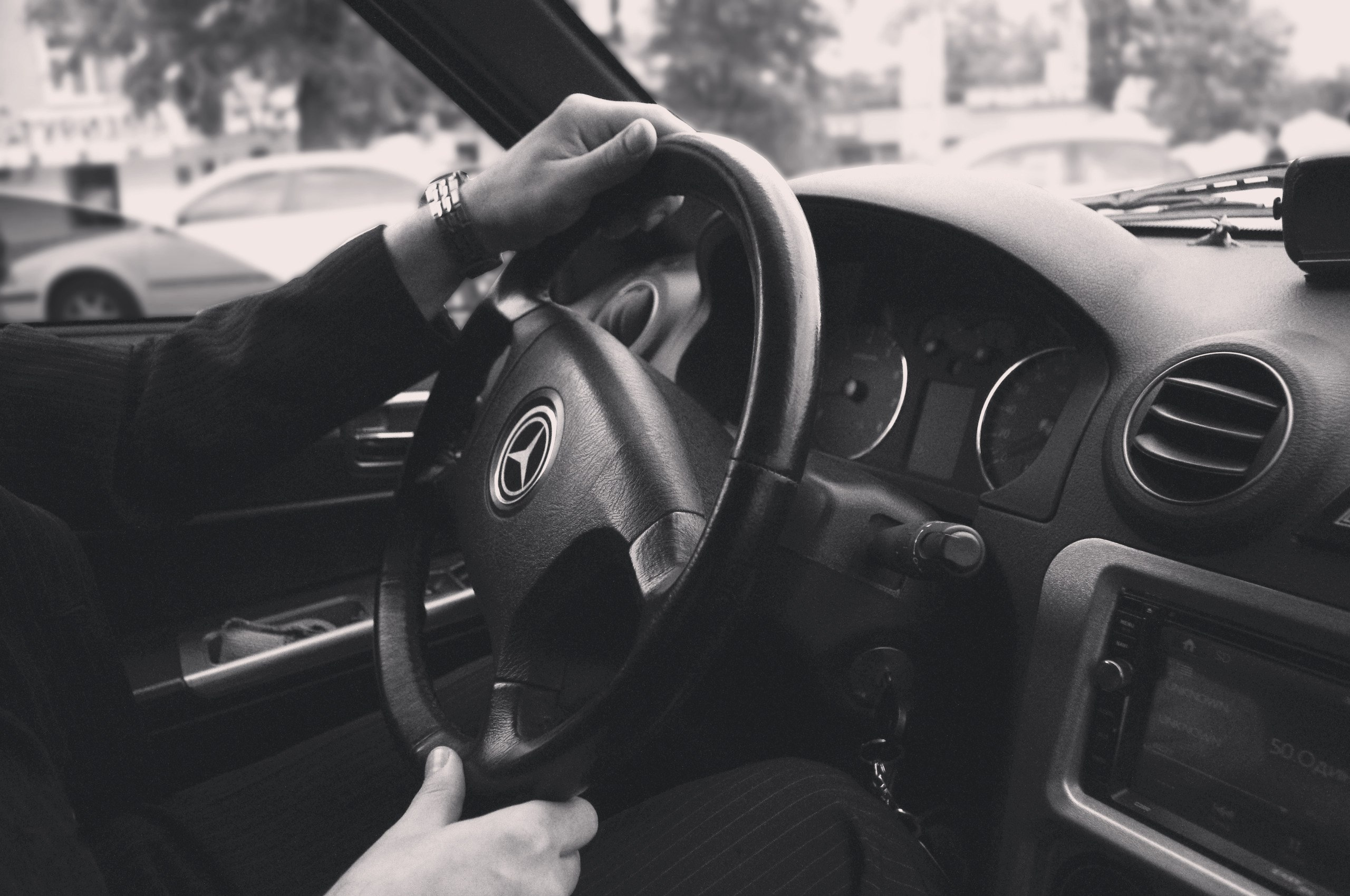 Grayscale Photography of Person Driving a Car