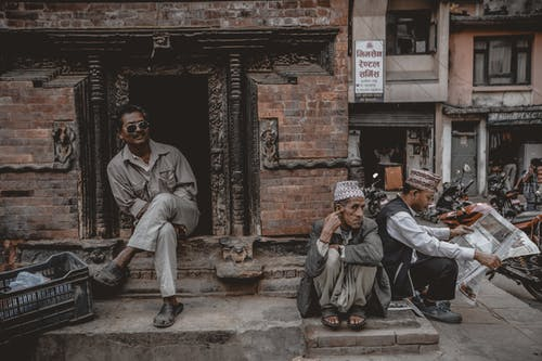 Full length Asian males sitting on stone ground against shabby brick building located on poor city street