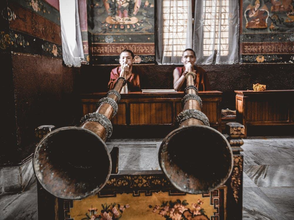 Man Tibetan musicians playing dungchen instrument in temple