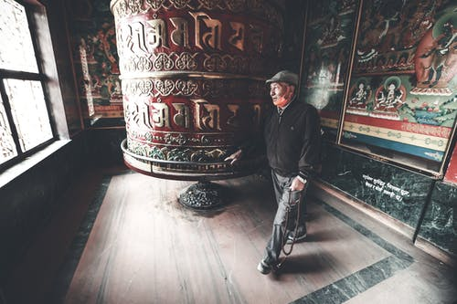 Full body contemplative elderly Asian male wearing casual outfits walking around prayer wheel in authentic religious temple