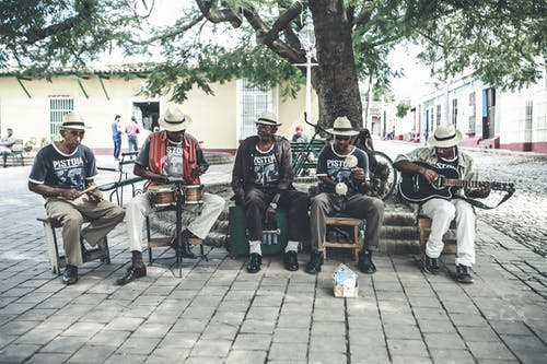 Adult ethnic male street band performing song on street