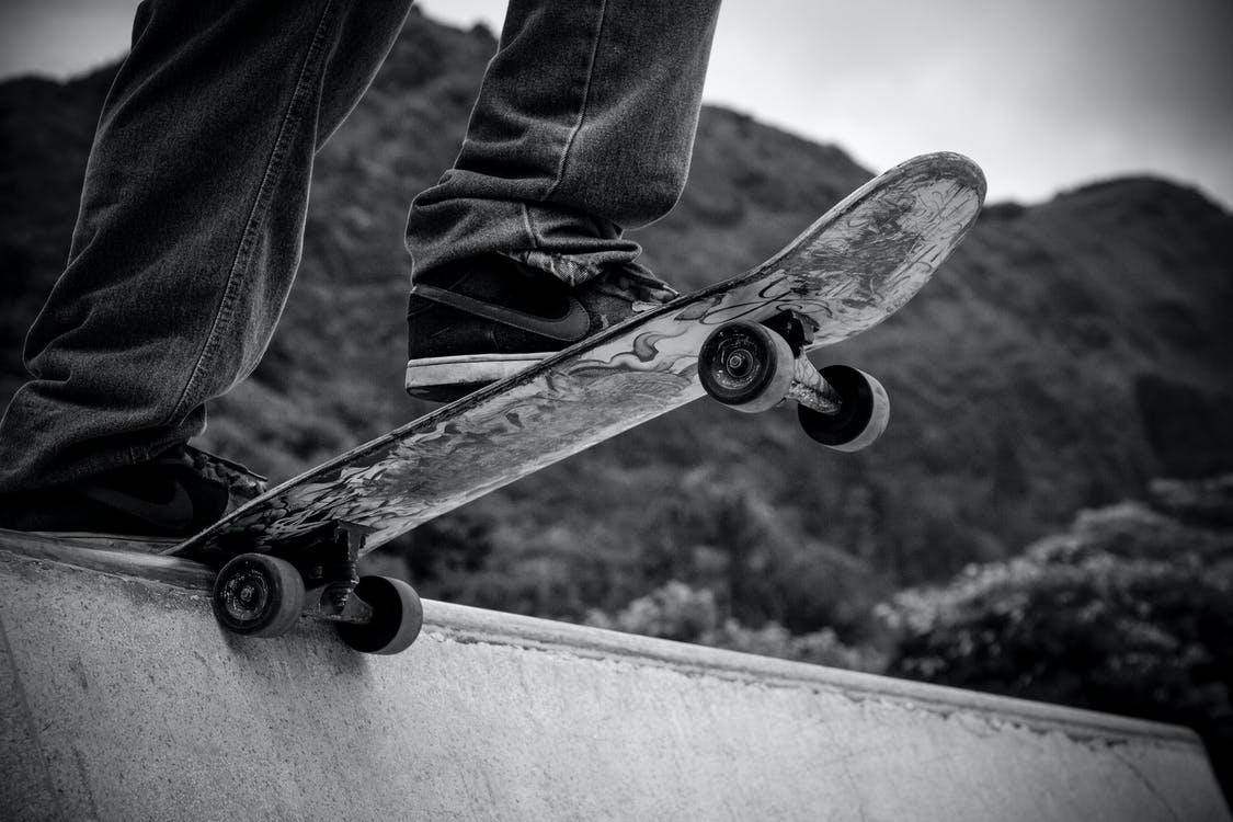 Person Standing on Skateboard Grayscale Photography