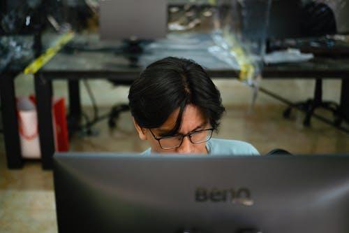 Man in Blue Shirt Wearing Eyeglasses Using Black Asus Laptop Computer