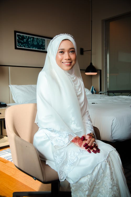 Woman in White Hijab Sitting on Bed