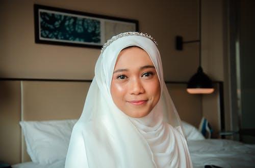 Woman in White Hijab Sitting on White Textile