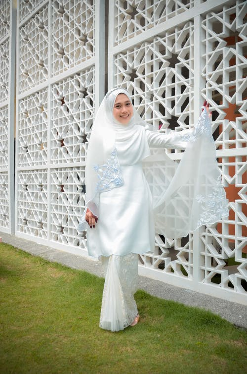 Woman in White Hijab Standing on Green Grass Field