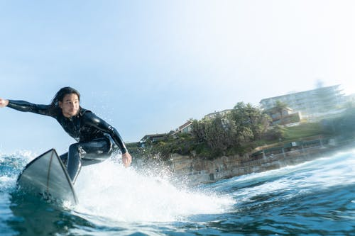 Man in Black Wetsuit Riding on White Surfboard