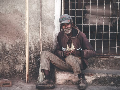 Poor senior Asian man sitting on street