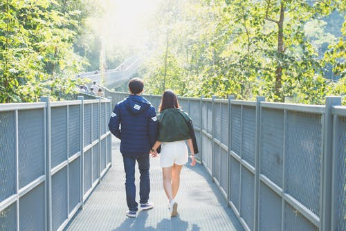 Man and Woman Holdings Hands While Walking on Bridge