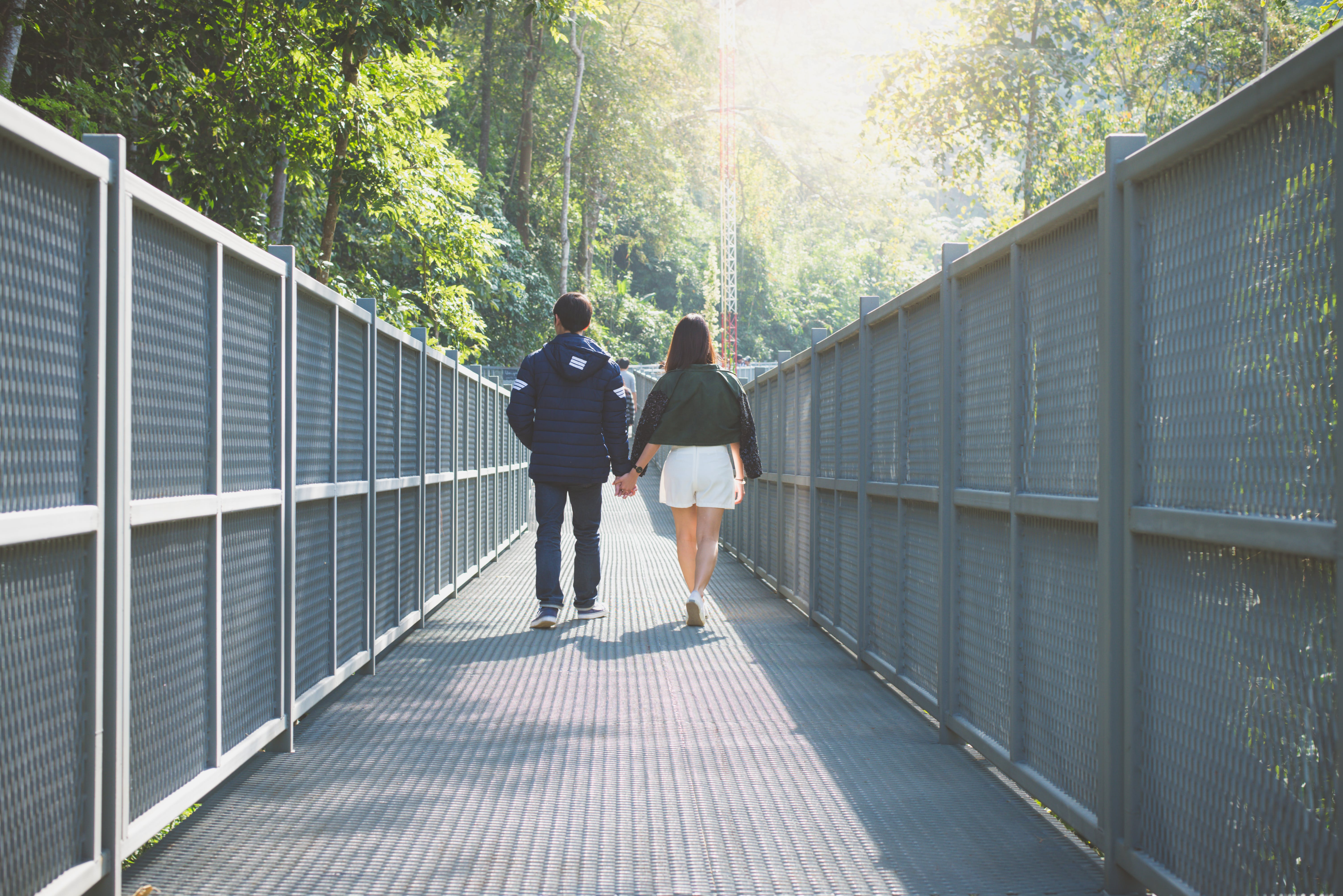 Man and Woman Holding Hand Walking on Grey Bridge