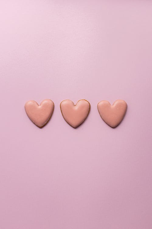 Small heart cookies on pink surface