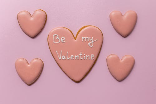 Top view of sweet heart shaped cookies saying Be My Valentine on pink background