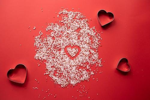 En Forma De Corazón Rojo Con Polvo Blanco Sobre Superficie Roja