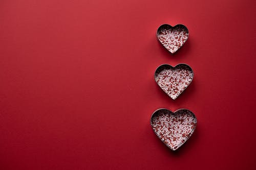Top view of different hearts forms for cooking with sprinkling on red background