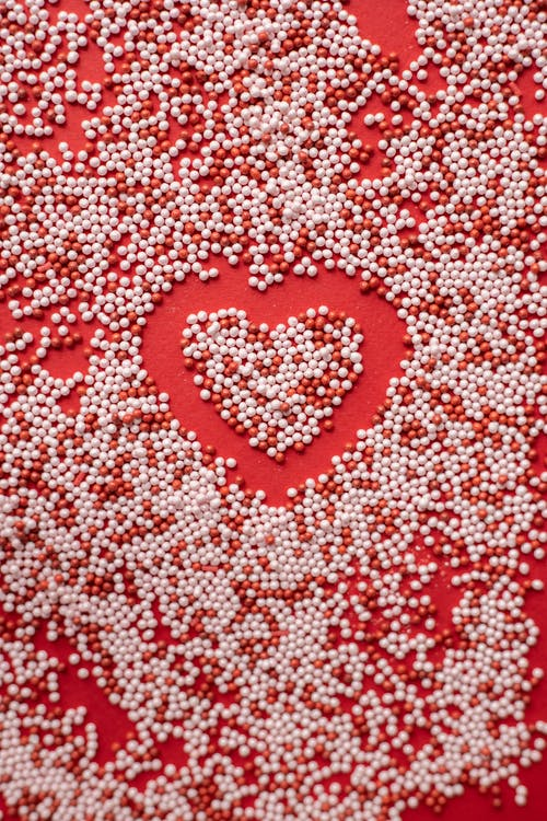 Top view of heart shape in scatter sprinkling on red background for Valentine day