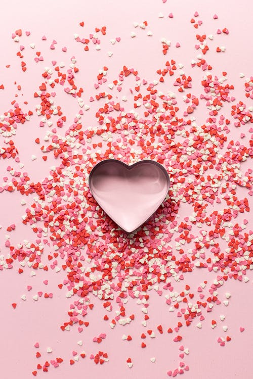 Top view of decorative heart shaped confetti scattered around box on pink background for Valentines Day