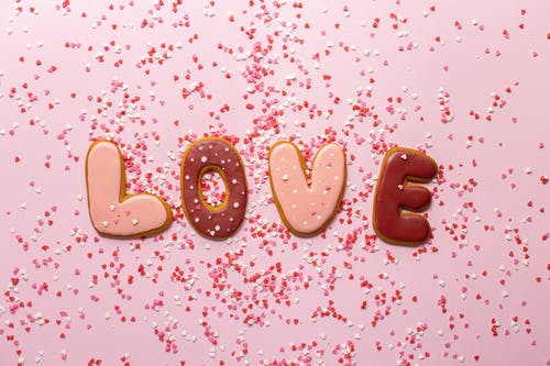 Top view of composed cookies making Love inscription with small heart shaped confetti on pink background
