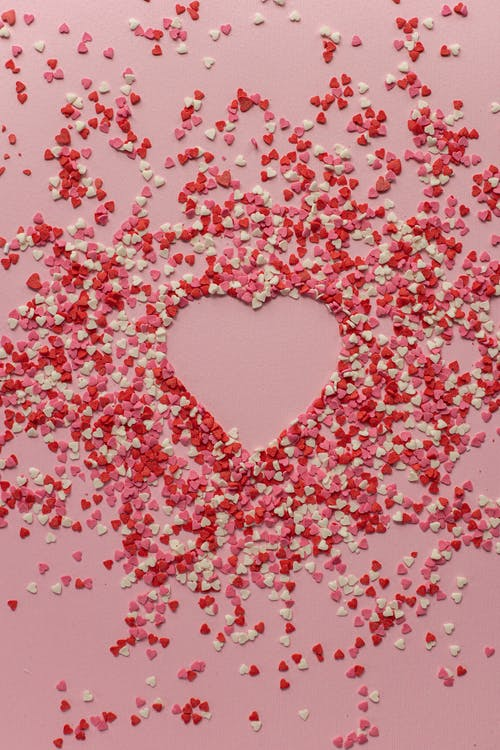 Paper hearts scattered on pink background